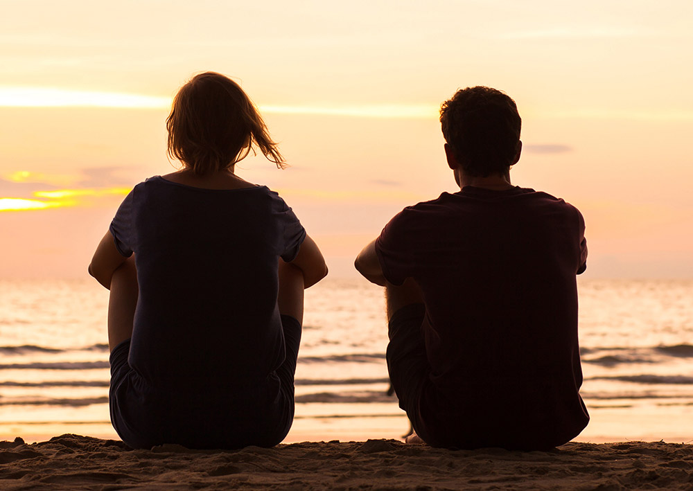 A man and woman sit on the beach looking at the ocean at sunset
