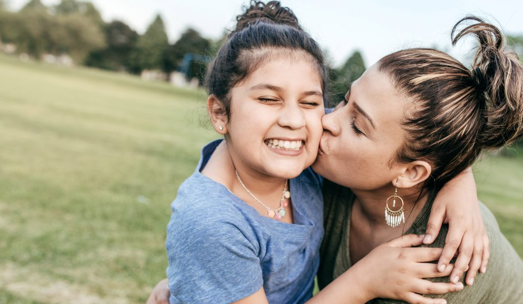 Mother bends down to kiss her daughter on the cheek while at a park