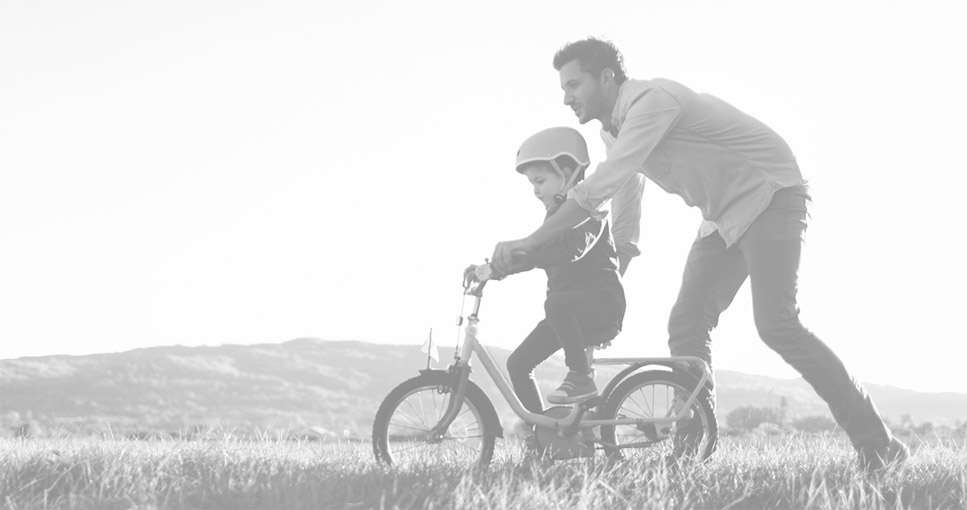 Father is teaching his child how to ride a bicycle